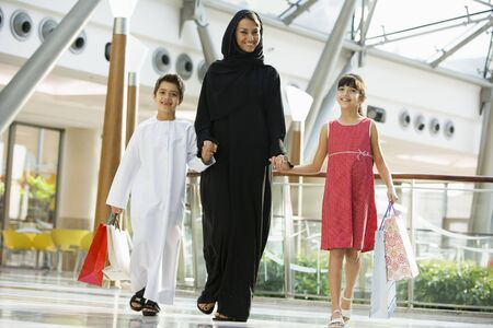 ni�os caminando: Mujer y dos ni�os peque�os en el centro comercial caminando sonriente (atenci�n selectiva)  Foto de archivo