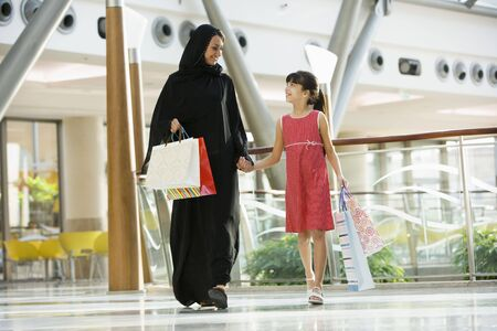 Woman and young girl walking in mall smiling (selective focus) Stock Photo