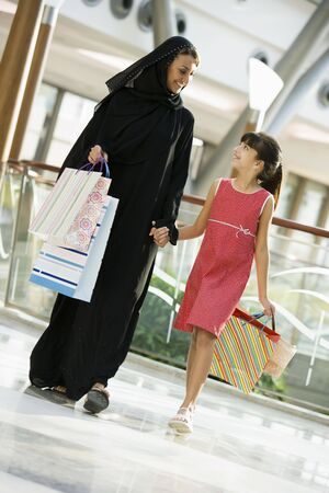 Woman and young girl walking in mall smiling (selective focus) Stock Photo - 3186630