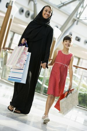jilaabah: Woman and young girl walking in mall smiling (selective focus) Stock Photo