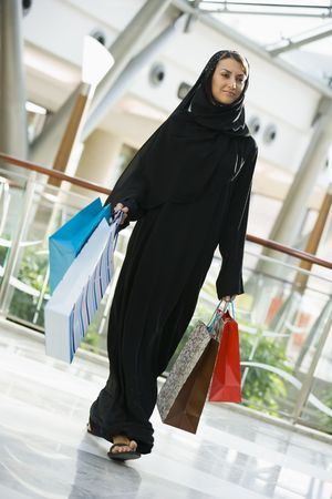 windowpanes: Woman walking in mall smiling (selective focus) Stock Photo