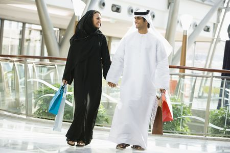 kanduras: Couple walking in mall holding hands and smiling (selective focus) Stock Photo