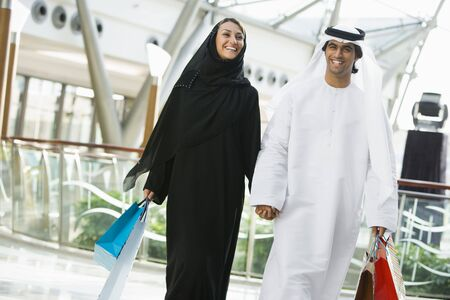 igals: Couple walking in mall holding hands and smiling (selective focus) Stock Photo