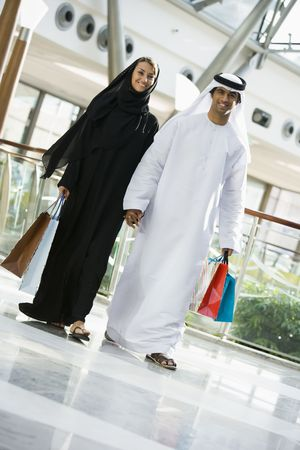 dishdashas: Couple walking in mall holding hands and smiling (selective focus) Stock Photo