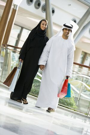 Couple walking in mall holding hands and smiling (selective focus) Stock Photo
