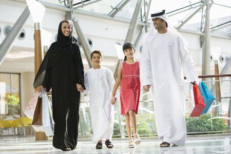 thobes: Familia mall caminando en la mano y sonriendo (atenci�n selectiva)  Foto de archivo