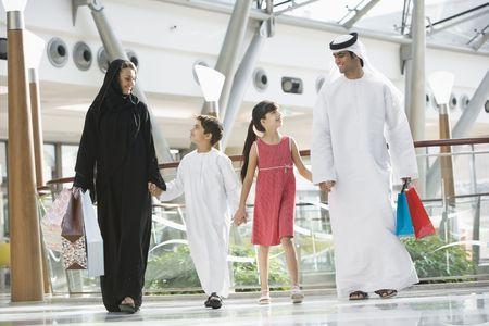 femmes muslim: Marchant dans la famille centre commercial se tenant par la main et souriant (s�lective focus)  Banque d'images