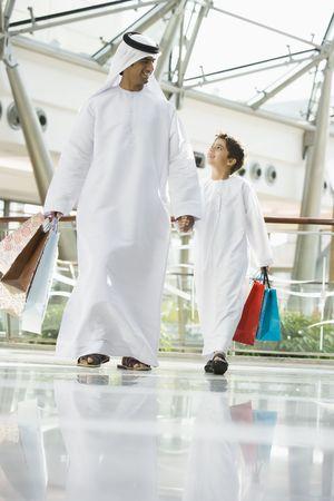 thawbs: Hombre y ni�o caminando en centro comercial la mano y sonriendo (atenci�n selectiva)  Foto de archivo