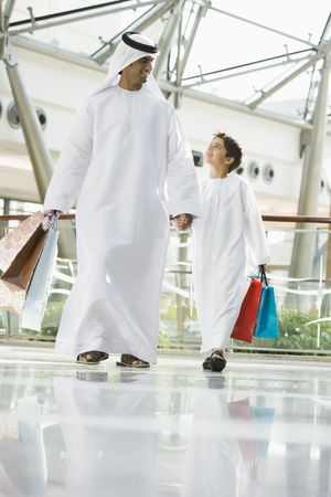Man and young boy walking in mall holding hands and smiling (selective focus) photo