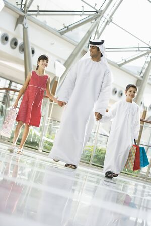 thobes: Man and two young children walking in mall holding hands and smiling (selective focus)
