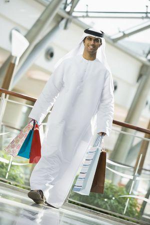 thobes: Hombre caminando en el centro comercial sonriente (atenci�n selectiva)  Foto de archivo
