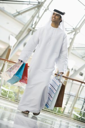 dishdashas: Man walking in mall smiling (selective focus) Stock Photo