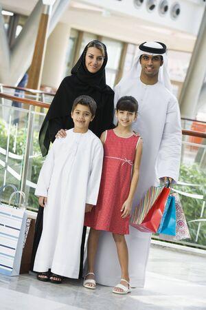middle eastern clothing: Famiglia in piedi in centro commerciale sorridente (attenzione selettiva)  Archivio Fotografico