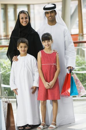 Family standing in mall smiling (selective focus)