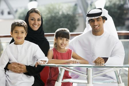 thobes: Family sitting indoors at table smiling (selective focus)