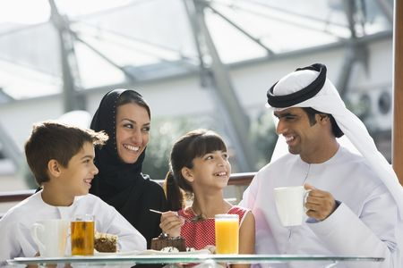 familia unida: Familia restaurante a comer postre y sonriente (atenci�n selectiva)