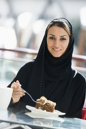 jilaabah: Woman at restaurant eating dessert and smiling (selective focus)