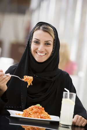 offset angles: Woman at restaurant eating spaghetti and smiling (selective focus)