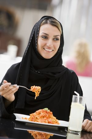 jilaabah: Woman at restaurant eating spaghetti and smiling (selective focus)