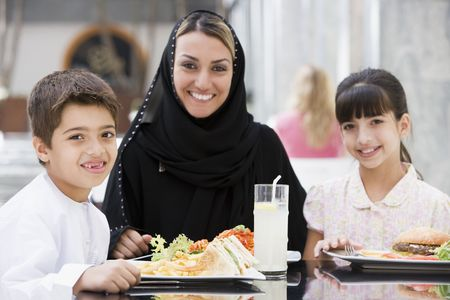 adult sandwich: Family at restaurant eating and smiling (selective focus) Stock Photo
