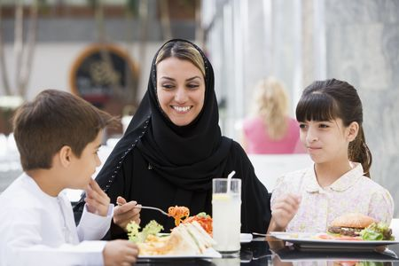 Woman and two young children at restaurant eating and smiling (selective focus) photo