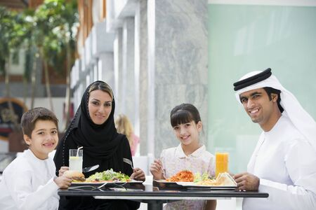 kanduras: Family at restaurant eating and smiling (selective focus) Stock Photo