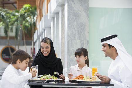 thobes: Familia restaurante a comer y sonriente (atenci�n selectiva)