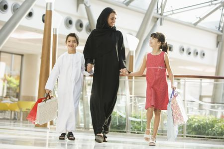 Woman and two young children walking in mall holding hands and smiling (selective focus)