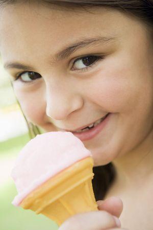 eating ice cream: Jovencita al aire libre, comer helado y sonriendo (atenci�n selectiva)  Foto de archivo