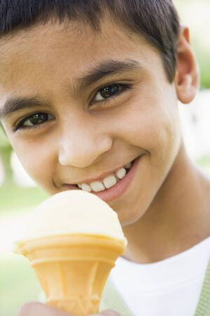Young boy outdoors eating ice cream and smiling (selective focus) photo