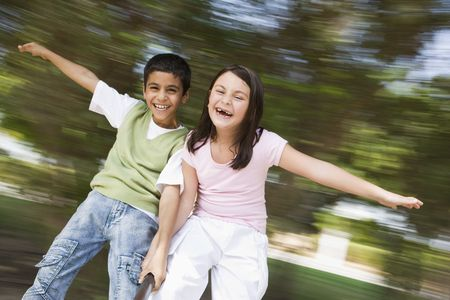 Two young children outdoors in playground spinning and smiling (blur) photo