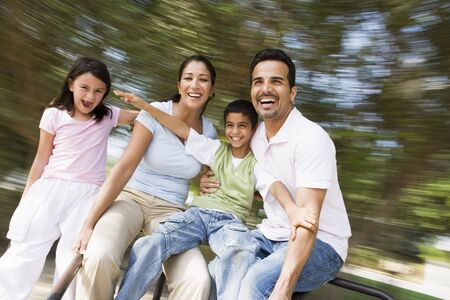 adult sisters: Family outdoors in playground spinning and smiling (blur)