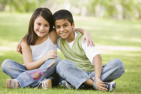 Two young children outdoors in park bonding and smiling (selective focus)