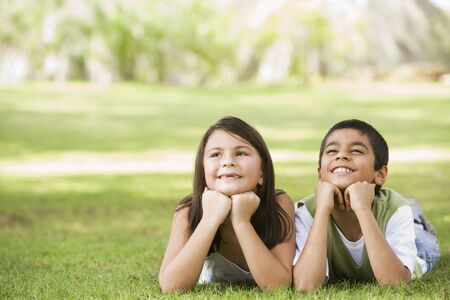 Two young children outdoors lying in park smiling (selective focus) photo