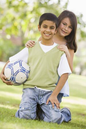 Two young children outdoors in park with ball smiling (selective focus) photo