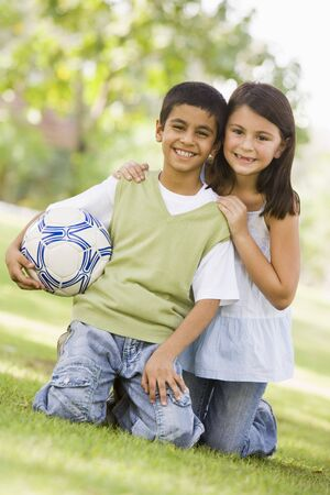 Two young children outdoors in park with ball smiling (selective focus) Stock Photo - 3186591