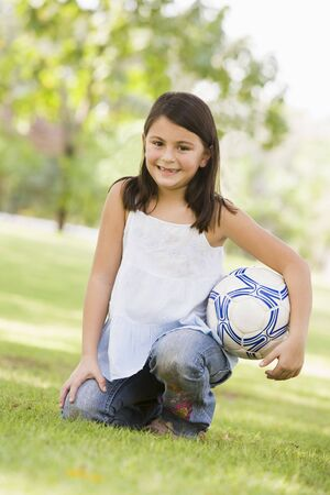 sporting activity: Young girl outdoors at park holding ball and smiling (selective focus)