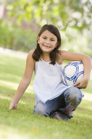 offset angles: Young girl outdoors at park holding ball and smiling (selective focus)
