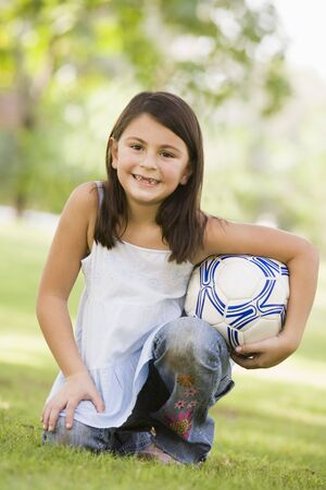 offset angle: Young girl outdoors at park holding ball and smiling (selective focus)