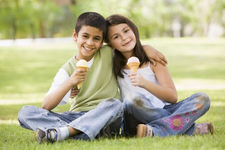 Two young children outdoors in park with ice cream smiling (selective focus) photo