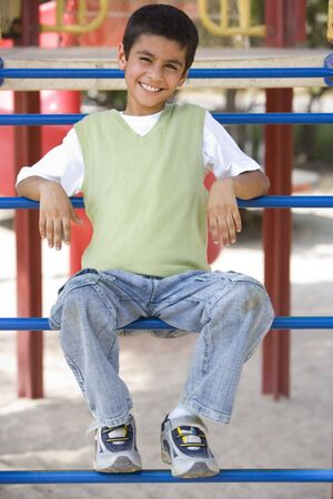 Young boy on playground structure smiling (selective focus) photo