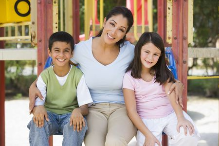 Mother and two young children sitting on playground structure smiling (selective focus) photo