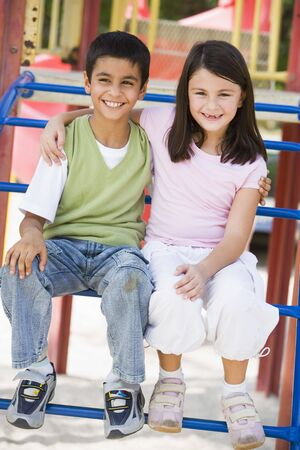 Two young children sitting on playground structure smiling (selective focus) photo