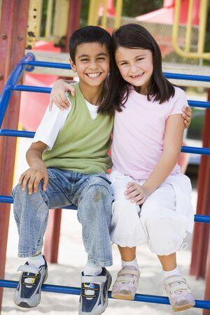 bambini seduti: Due i figli piccoli giochi seduta sulla struttura sorridente (messa a fuoco selettiva)
