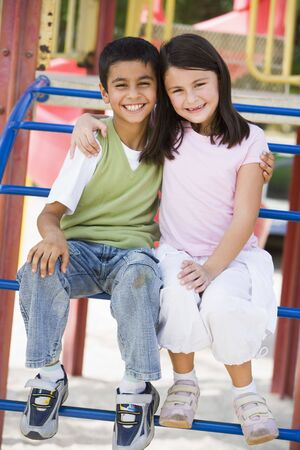 girl woman: Two young children sitting on playground structure smiling (selective focus) Stock Photo