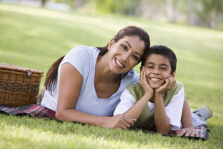 peacefulness: Mother and son outdoors in park with picnic smiling (selective focus)