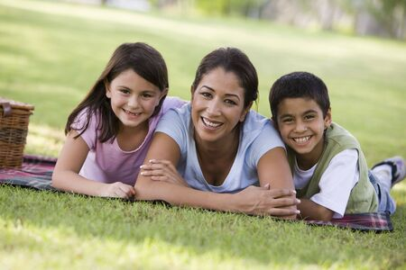 girl lying down: Mother and two young children outdoors in park with picnic smiling (selective focus)