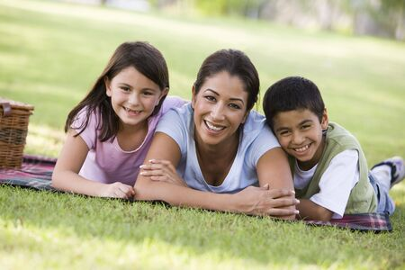 Mother and two young children outdoors in park with picnic smiling (selective focus) photo