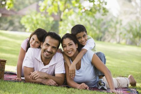 Family outdoors in park with picnic smiling (selective focus) photo