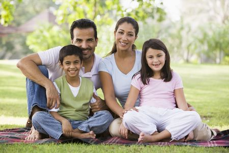 Family sitting outdoors in park smiling (selective focus) photo